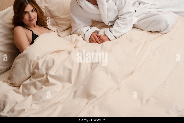 Couple laying on bed together - Stock Image
