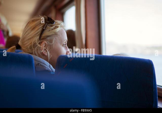 Sweden, Gothenburg Archipelago, Vastergotland, Styrso, Mature blonde woman looking through train window - Stock Image