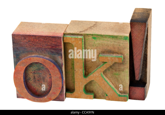 OK in vintage wooden letterpress type blcks, stained by color ink, isolated on white - Stock Image