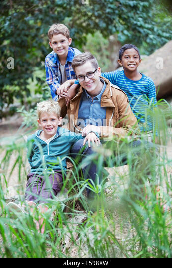 Students and teacher smiling in forest - Stock Image