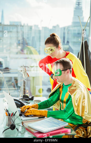 Superheroes working on laptop in office - Stock Image