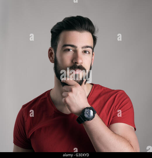 Puzzled young man stroking touching beard looking at camera over gray background - Stock Image