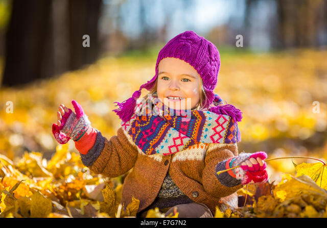 Little girl playing with autumn leaves - Stock Image