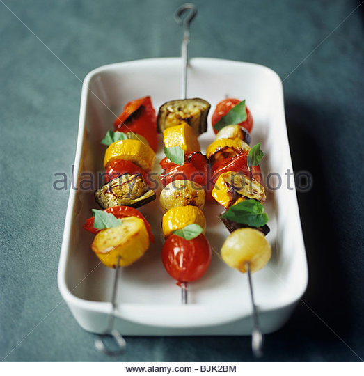 Three grilled vegetable kebabs (tomatoes, pepper, courgette) - Stock Image