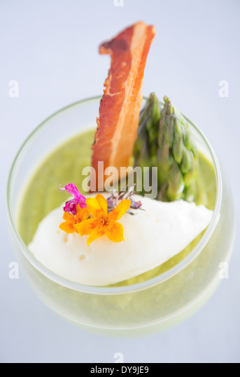Asparagus soup served in a glass, decorated with bacon, asparagus tips and flowers. - Stock Image
