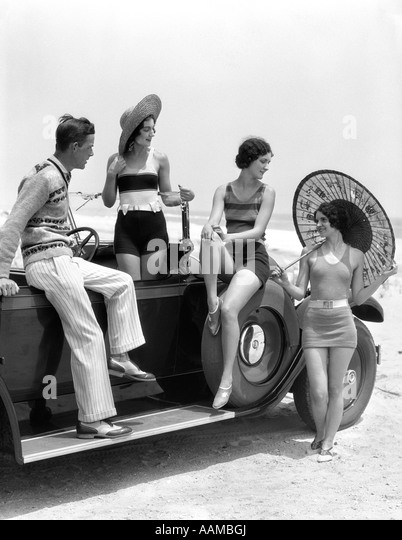 1920s 1930s MAN AND THREE WOMEN IN BEACH CLOTHES OR BATHING SUITS POSING WITH CAR ON RUNNING BOARD - Stock Image