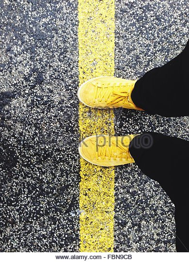 Low Section Of Man Standing On Yellow Road Marking - Stock Image