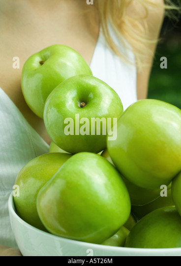 Woman holding bowl of apples, close-up of apples - Stock Image