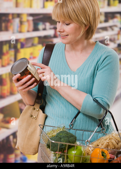 Woman reading food label in grocery store - Stock Image