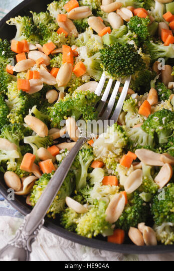 Dietary salad with broccoli, carrots and peanuts close-up on a plate. vertical top view - Stock Image