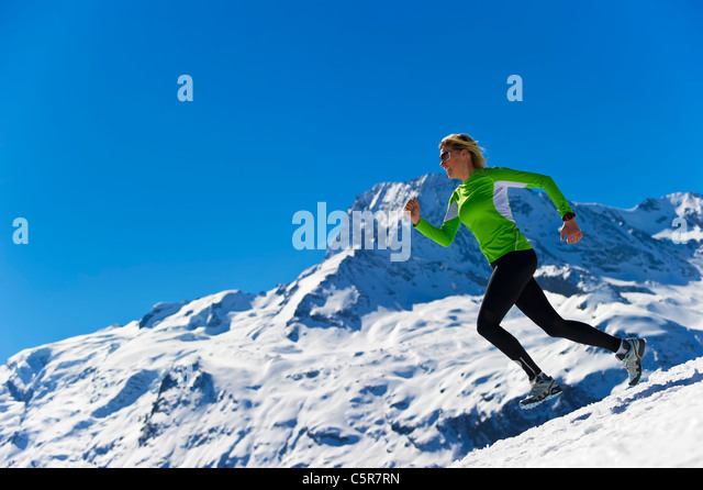 A woman jogging in high snowy alpine mountains. - Stock-Bilder