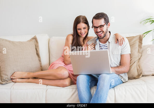 Hipster couple using laptop on couch - Stock Image