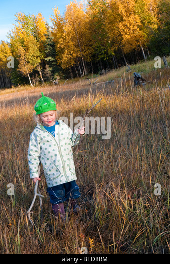 Female toddler wearing a green hat plays with driftwood sticks on the mud flats next to the Coastal Trail, Anchorage, - Stock Image
