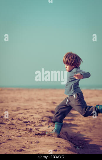 Morocco, Boy (8-9) playing and jumping on beach - Stock Image