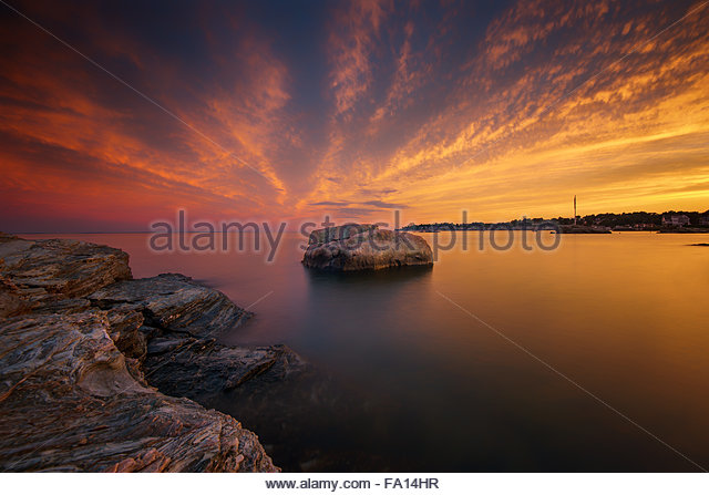A peaceful serene and warm New England seascape at sunset with beautiful rocks and colorful clouds with long exposure - Stock Image
