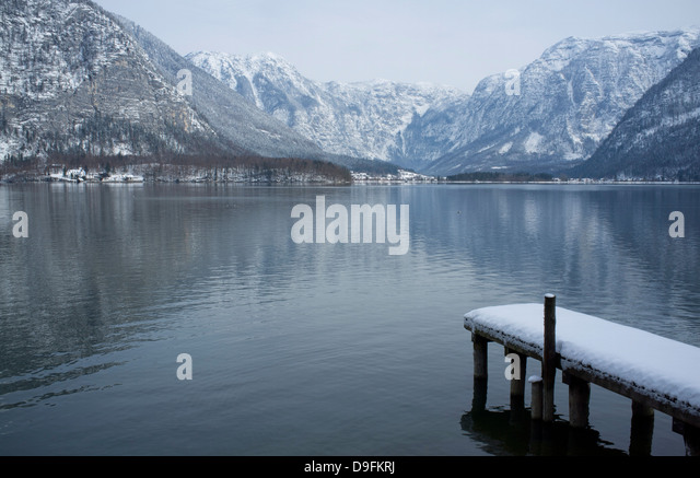 A snow covered dock and surrounding mountains on Halstatter See, Austria - Stock Image