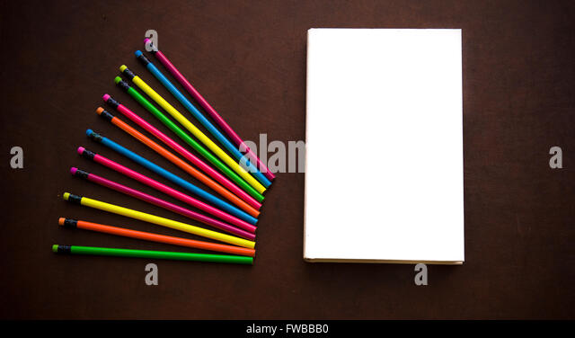 Wooden writer desktop with colorful pencil and withe empty cover book - Stock Image