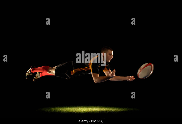 Rugby player diving and passing - Stock Image