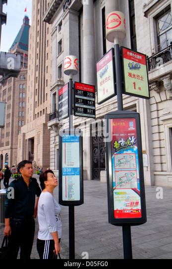 Shanghai China Huangpu District The Bund Zhongshan Road bus stop signs route information Asian man woman Art Deco - Stock Image
