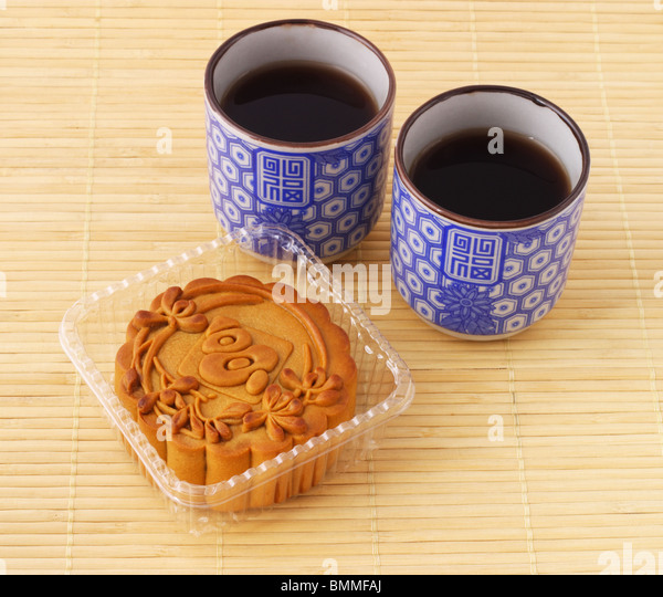 Chinese mid autumn festival moon cake and tea on bamboo mat - Stock Image