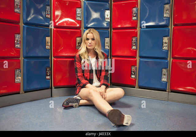 A young woman in front of some red and blue lockers. - Stock Image