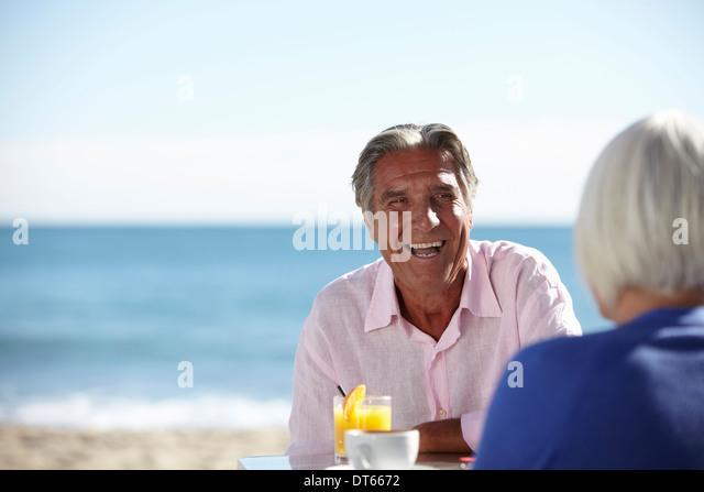Couple enjoying wine by seaside - Stock Image
