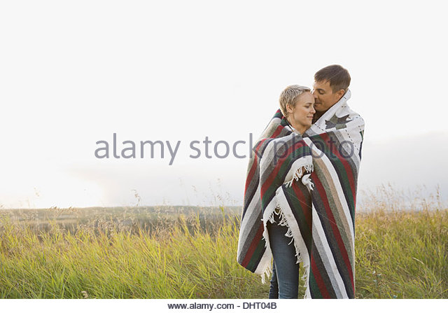 Loving mid adult couple wrapped in blanket at field - Stock Image