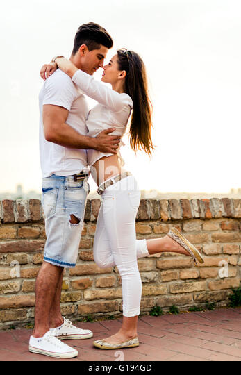 Young romantic couple hugging and about to kiss in beautiful sunset - Stock-Bilder
