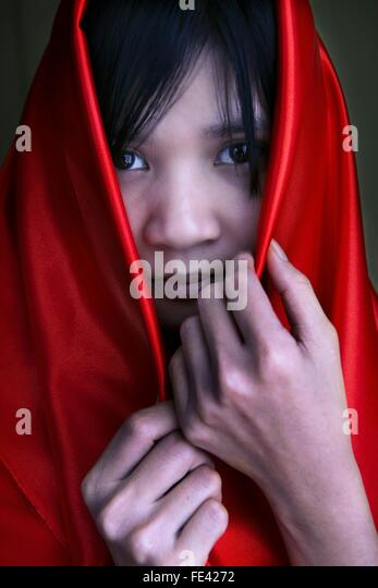 Portrait Of Young Woman Covered In Red Scarf - Stock Image