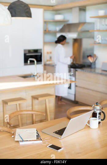 Laptop, French press coffee, cell phone and notebook on kitchen table - Stock Image