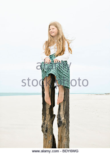 Girl sitting on top post - Stock Image