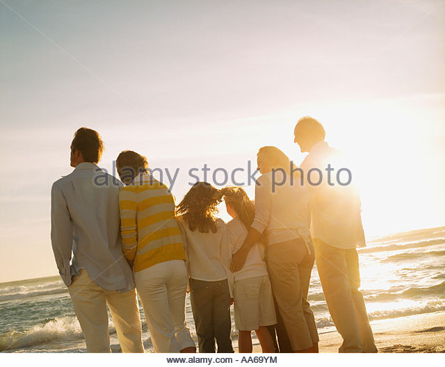 Multigenerational family portrait outdoors at sunset - Stock-Bilder