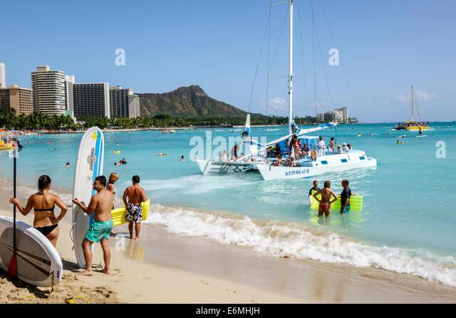 Waikiki Beach Honolulu Hawaii Hawaiian Oahu Pacific Ocean waterfront sunbathers surfboard Kepoikai II catamaran - Stock Image