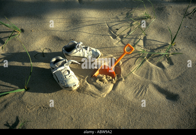 Beach with childrens tennis shoes and orange plastic shovel - Stock Image
