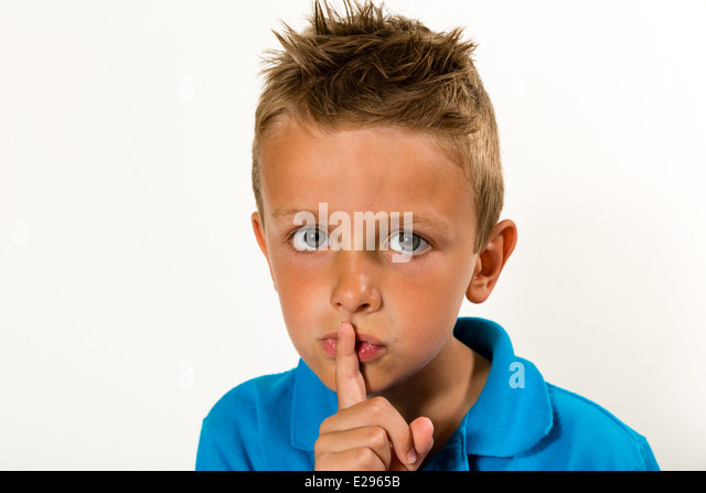 Caucasian boy doing a Please Keep Quiet gesture towards the camera. Studio shot with white background. - Stock Image