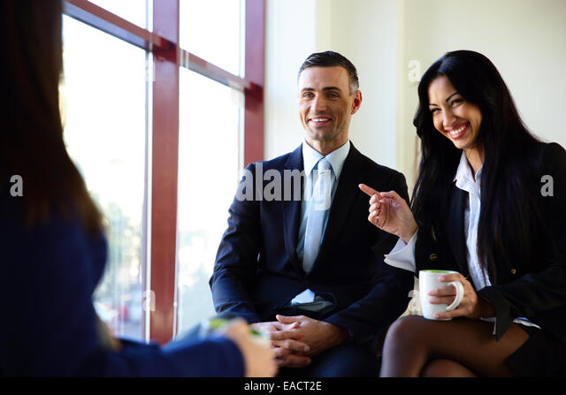 Smiling businesspeople having coffee break in office - Stock Image