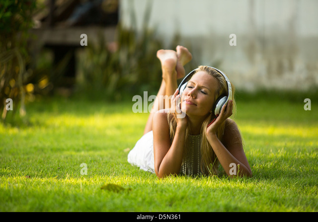 Emotional a lovely girl with headphones enjoying nature and music at sunny day. - Stock Image