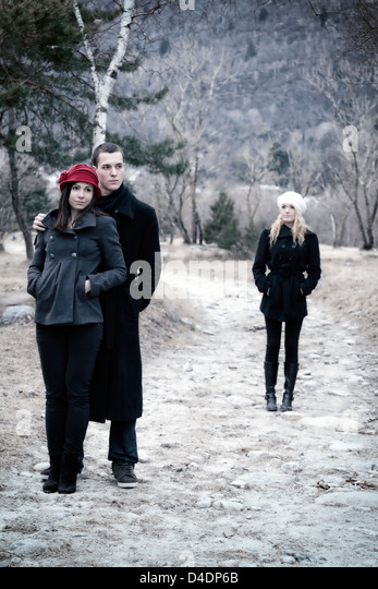 a couple arm in arm and a second woman is left behind - Stock-Bilder