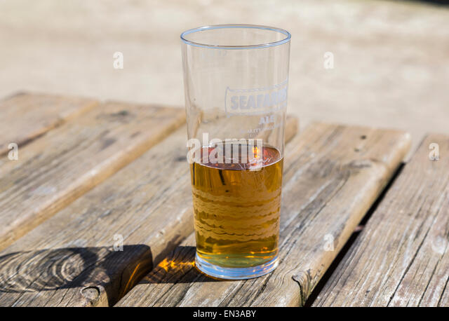 Half empty, or half full, glass of beer or shandy on a wooden pub table, glass marked Seafarer's Ale - Stock Image