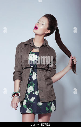 Trendy Fashion Model in Elegant Clothes holding her Tress - Stock Image