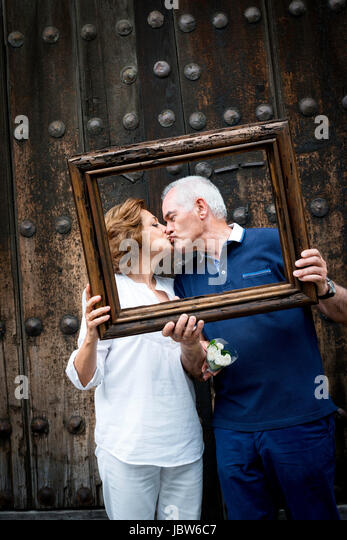 Portrait of senior couple, kissing, holding wooden frame in front of their faces, Mexico City, Mexico - Stock-Bilder