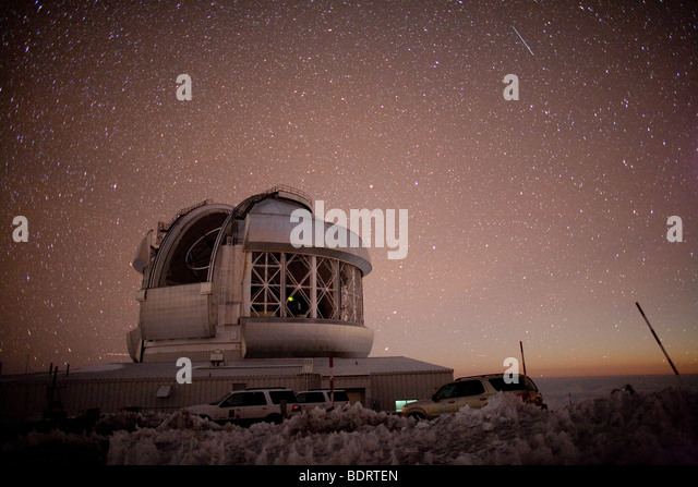 Nighttime on Mauna Kea, showing the Gemini telescope with the light from moonrise visible in the east - Stock Image