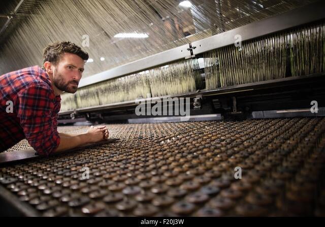 Male weaver monitoring old weaving machine in textile mill - Stock-Bilder