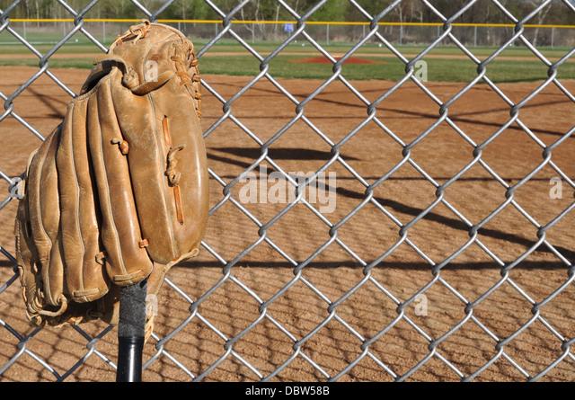 Baseball bat and glove with baseball field behind - Stock Image