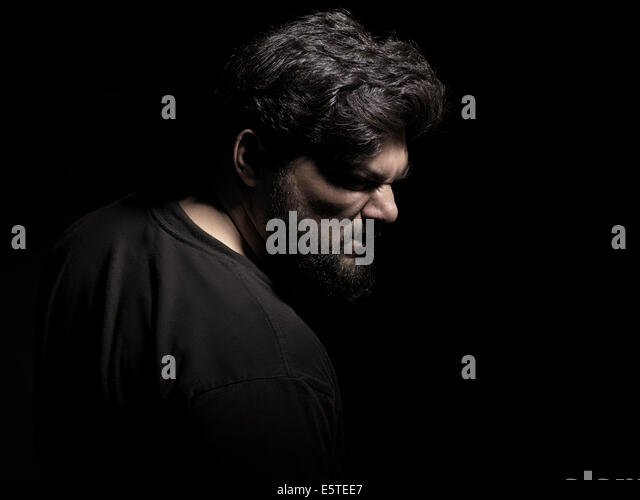 Dramatic portrait of an angry middle aged man isolated on black background - Stock Image