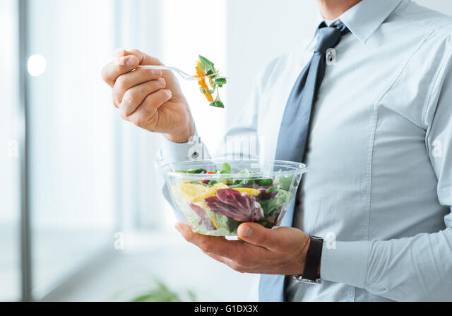 Businessman having a vegetables salad for lunch, healthy eating and lifestyle concept, unrecognizable person - Stock Image