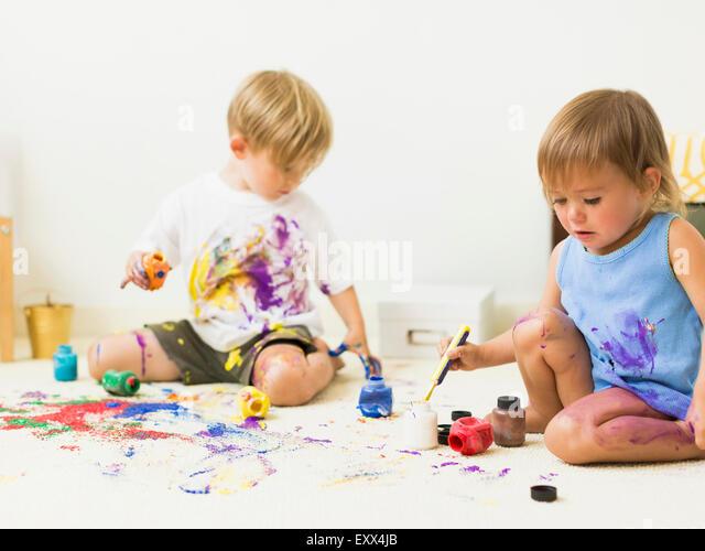Children (2-3) painting on carpet - Stock Image