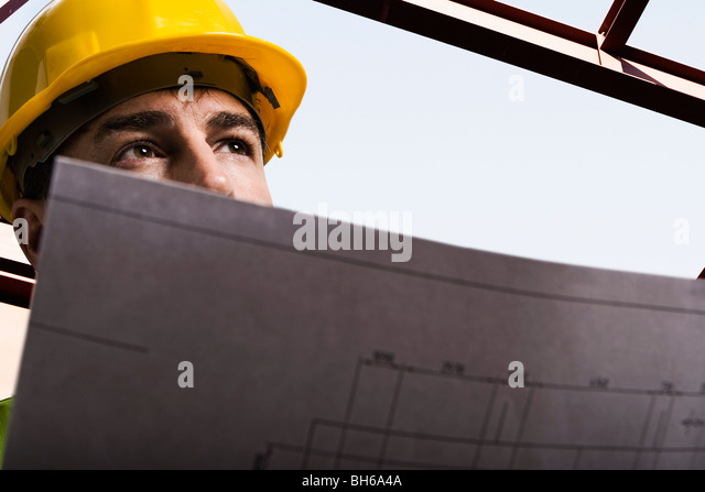 Construction worker holding drawings - Stock Image