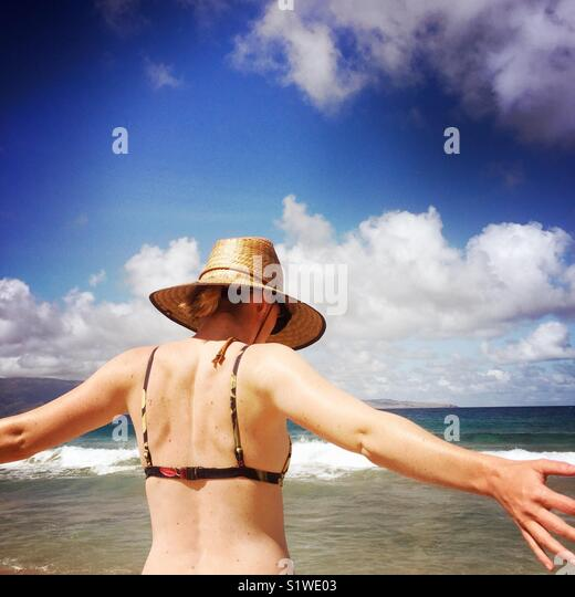 A young women spreading out her arms on the beach. Kapalua, Maui Hawaii USA. - Stock Image