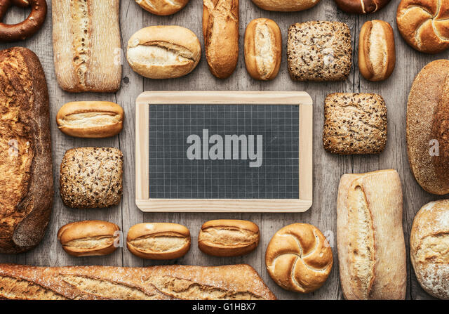 Fresh crisp bread on a wooden worktop and blank chalkboard, bakery and healthy eating concept, flat lay banner - Stock Image